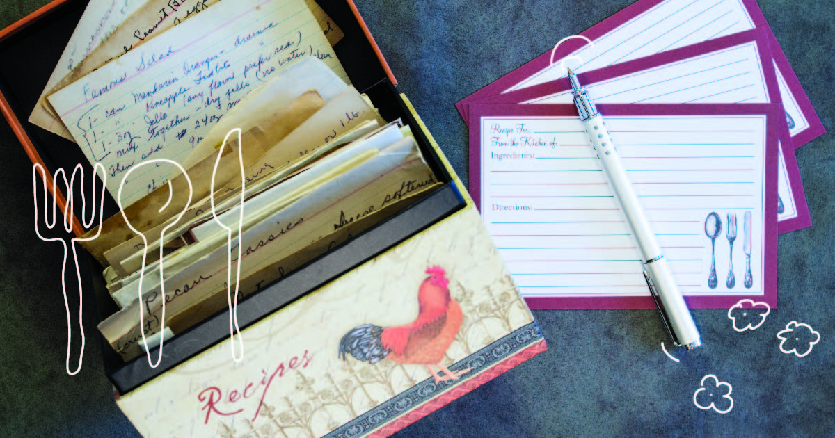A recipe box decorated with a red rooster. Hand-written recipe cards are piled inside it, and blank ones sit with a pen beside it.